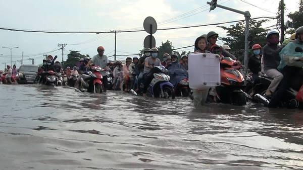 báo VietNamNet đưa tin, đoạn gần chân cầu Bình Điền nước ngập hơn nửa mét khiến hàng loạt phương tiện chết máy. Nhiều người cho biết, mặt đường ngập lênh láng nước nên họ bị té ngã do sụp ổ voi, ổ gà. Ảnh: VietNamNet