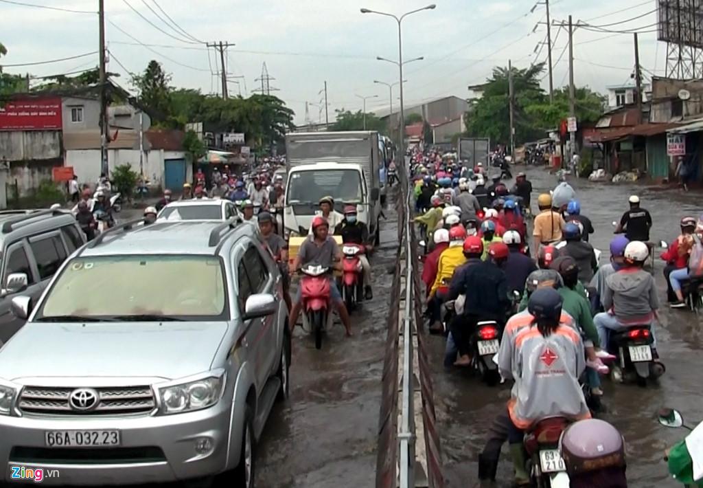 Cảnh sát giao thông vất vả lội nước, vừa phân luồng vừa hỗ trợ những người bị té ngã. Ảnh: Zing.vn