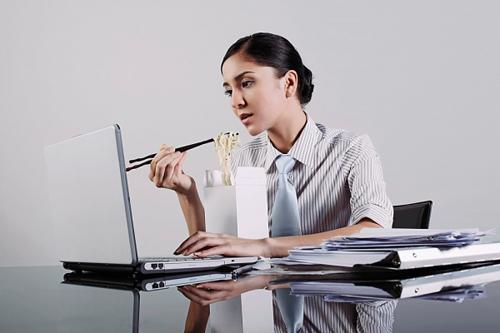 Dân văn phòng thường có thói quen vừa ăn vừa làm việc dẫn đến đau dạ dày. Ảnh minh họa