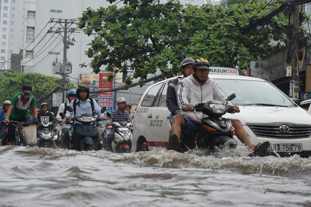 Đường Nguyễn Xí (Q.Bình Thạnh) tại khu vực từ giao lộ với đường Đinh Bộ Lĩnh tới gần cầu Đỏ, nước ngập hơn nửa bánh xe khiến hàng loạt phương tiện chết máy phải dắt bộ. Ảnh: Lao Động
