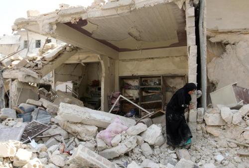 Tình hình chiến sự Syria mới nhất: Một phụ nữ đứng giữa đống đổ nát sau một cuộc không kích vào vùng Bab al-Nairab do phiến quân kiểm soát ở thành phố Aleppo, Syria
