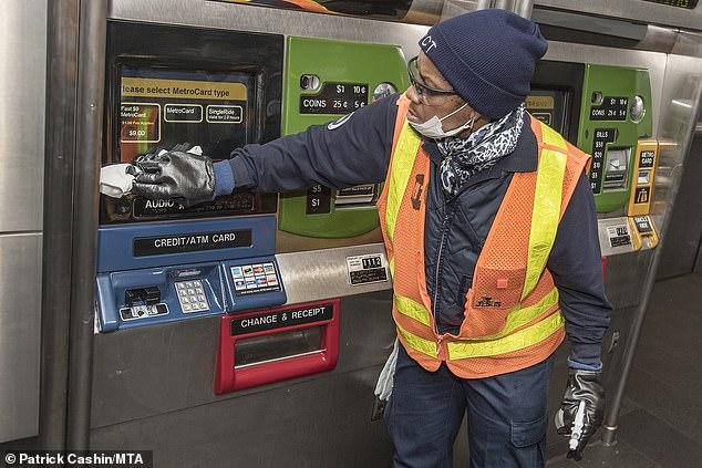 Nhân viên vệ sinh bề mặt máy ATM tại New York, Mỹ.