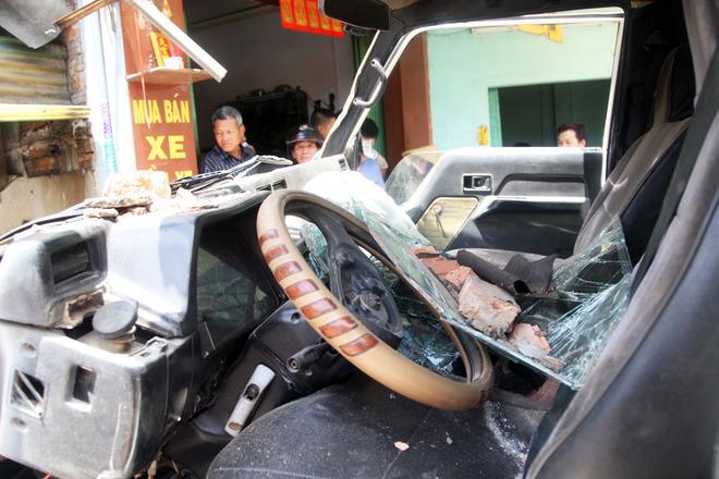 Đầu xe ben hư hỏng nặng, kính xe bể, tường căn nhà lọt vào bên trong cabin. Sau tai nạn, tài xế Trực bị tạm giữ, còn phụ xe bỏ trốn.