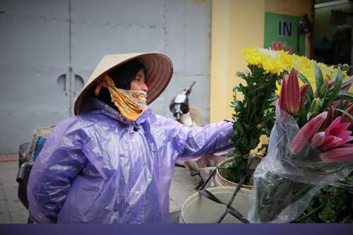 Giữa cái lạnh buốt giá, người phụ nữ này vẫn chở những gánh hàng hoa đi khắp phố vì kế mưu sinh. Ảnh: Tiền Phong
