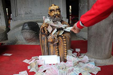 Nhét tiền vào tay Phật