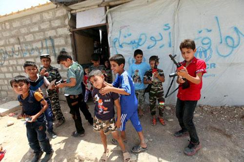 Trẻ em Iraq chơi cùng những khẩu súng đồ chơi phía ngoài một trại tị nạn ở ngoại ô thành phố Arbil hôm 17/7