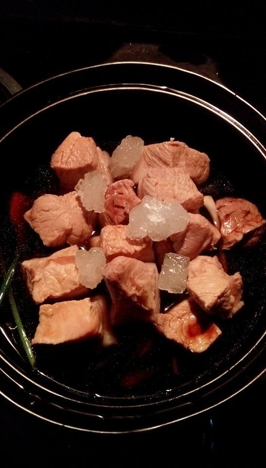 Xếp gừng và hành dưới đáy nồi rồi cho thịt, xì dầu, đường phèn vào kho