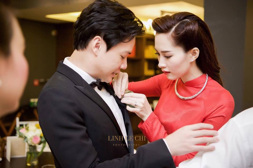 Đặng Thu Thảo khéo léo chỉnh hoa cài áo cho chồng. Ảnh: Lê Chí Linh