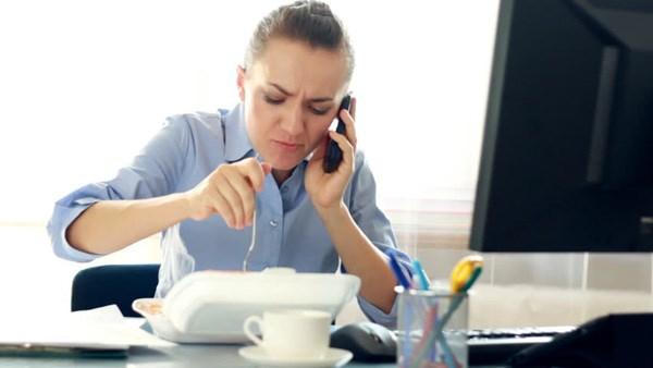 Ăn trưa tại bàn làm việc là thói quen nhiều người mắc. Ảnh minh họa