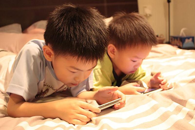 Trẻ dùng điện thoại di động có nguy cơ nhiễm hội chứng TIC ((giật cơ mắt tăng cao). Ảnh minh họa