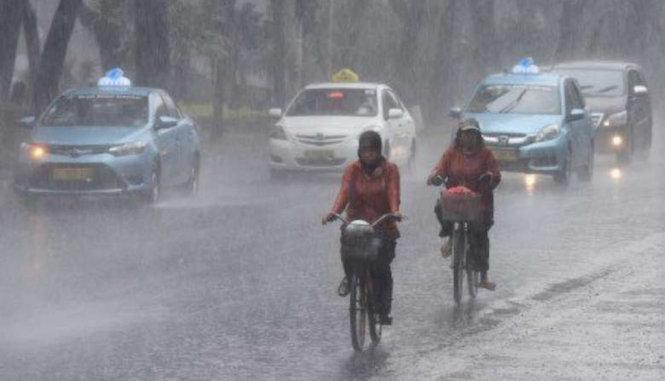 Hai phụ nữ đạp xe trong cơn mưa lớn tại tỉnh miền Trung Java. Ảnh: JAKARTA POST