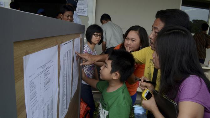 Danh sách hành khách được dán bên trong một trung tâm khẩn cấp tại sân bay Juanda ở Surabaya, Indonesia.