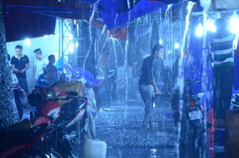 """Mưa như trút nước khiến gần 500 gian hàng của 'Festival Nông nghiệp năm 2015' tổ chức tại Công viên Gia Định phải """"ngâm chân"""" trong nước. Rất nhiều chủ gian hàng đã dầm mình trong mưa, vật vã chất đồ lên cao. Ảnh: Phước Tĩnh"""