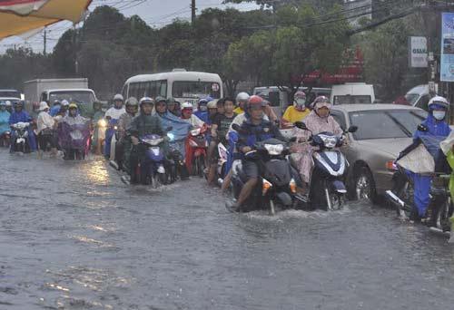 Nhiều người tìm cách tránh đoạn ngập đã lưu thông lộn xộn trong làn ô tô hoặc đi lên vỉa hè khiến giao thông trở nên hỗn loạn và nguy cơ xảy ra tai nạn rất cao. Ảnh Vietnamnet