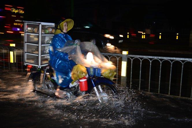 Một người bán bánh mì chạy xe qua đoạn đường ngập ở Q. Bình Tân