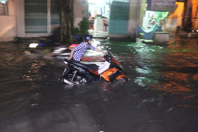 Một thanh niên đẩy xe chết máy giữa mênh mông biển nước trên đường An Dương Vương, Q.6