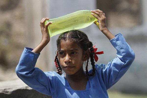 Một học sinh Ấn Độ đội chai nước lên đầu để xoa dịu cái nắng nóng kỷ lục