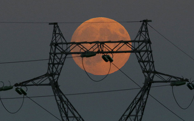 Trăng máu là hiện tượng 'nguyệt thực toàn phần', xảy ra khi Trái Đất nằm giữa Mặt Trời và Mặt Trăng và cả 3 cùng nằm trên cùng một đường thẳng. Hình ảnh Mặt Trăng khổng lồ xuất hiện trên đường điện cao thế ở Le Pallet, Pháp