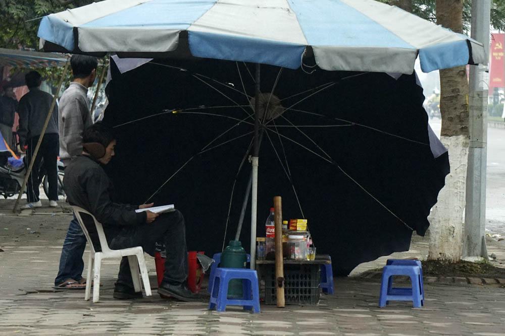 Một quán cóc ven đường nghiêng ô không để che nắng mà để chắn đợt gió mùa ào ạt thổi. Ảnh: Dân Trí