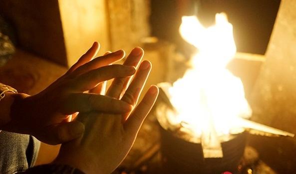 Nhiều người đi đường đã phải dừng lại, đến gần những bếp lửa để sưởi ấm cho bớt lạnh rồi mới lên đường đi tiếp. Ảnh: Infonet