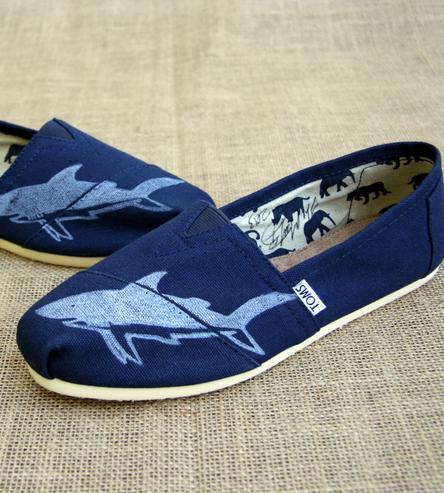 Giày Toms in họa tiết cá mập: Đôi giày với họa tiết cá mập được in thủ công màu trắng nổi bật trên nền vải canvas sắc xanh dương này sẽ giúp bạn trông vô cùng khỏe khoắn và phong cách. Chúng có giá $85 trên trang scoutmob.com.