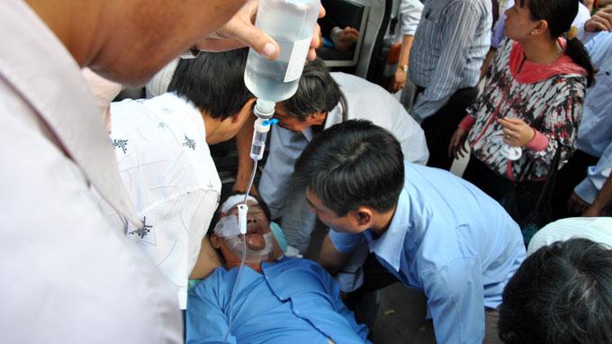 Một nạn nhân bị tạt axít được đưa đi cấp cứu. Ảnh: Thái An