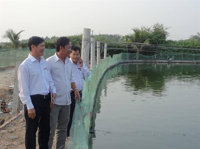 Nguyễn Văn Thêm (giữa) đang đưa khách đi tham quan các ao cá. Ảnh: Nông nghiệp Việt Nam