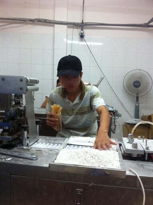 Công nhân vừa ăn vừa dùng tay trần đưa thực phẩm chức năng viên vào máy dập vỉ.