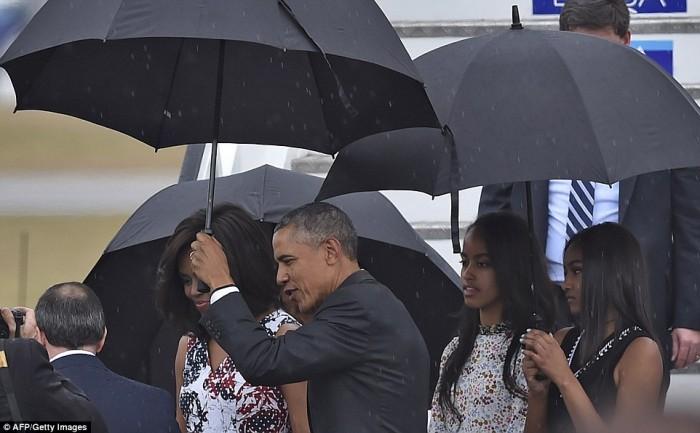 Ngoài sự hài hước, ông Obama còn được biết đến là người chồng rất thương yêu vợ con. Ông che ô cho vợ trong một cơn mưa nặng hạt.