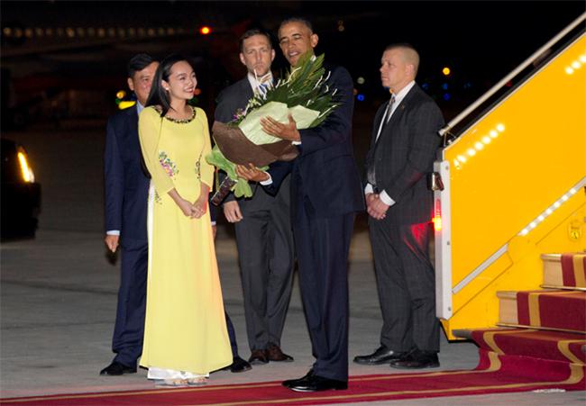 Tổng thống Barack Obama vui vẻ nhận bó hoa tươi từ đoàn tiếp đón của Việt Nam trao tặng (Ảnh Reuters)