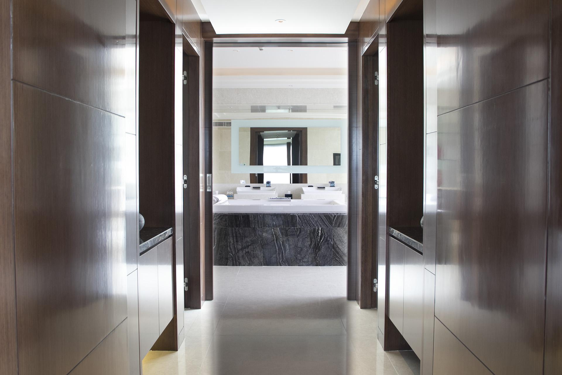 Phòng tắm thiết kế với một bể sục lớn, hai buồng tắm đứng và bàn trang điểm lớn ở cửa sổ.