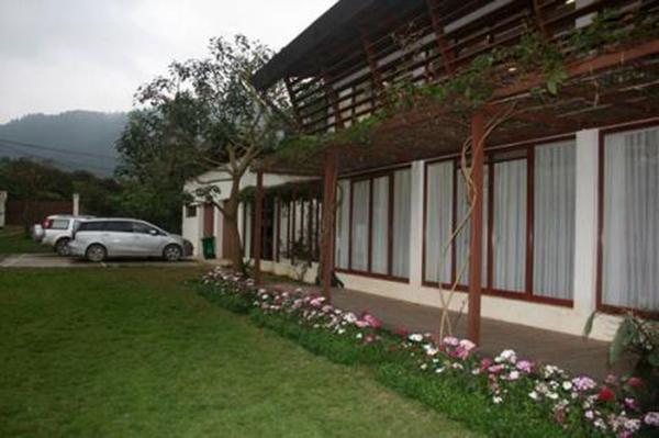 Bãi đỗ xe nằm sát cạnh khu vườn cỏ với những khóm hoa xinh.