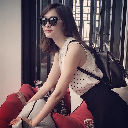 Thu Thảo chọn áo voan cổ tròn không tay họa tiết chấm bi và chân váy đen xòe cổ điển cho chuyến du lịch tại Đà Nẵng gần đây.