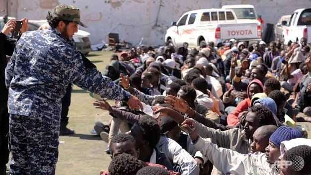 Những người di cư nhận nước uống tại một trung tâm giam giữ ở Tripoli
