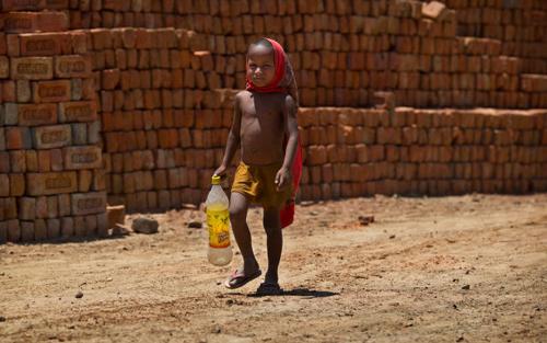 Một chú bé đi dưới cái nắng như thiêu để lấy nước ở ngoại ô New Delhi