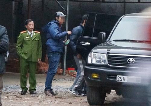 Cảnh sát đưa người liên quan lên xe ô tô