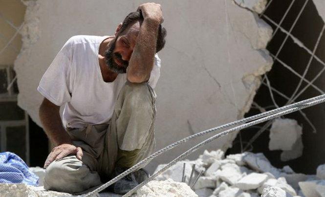 Một người đàn ông suy sụp giữa đống đổ nát của một tòa nhà bị không kích ở Syria, theo tình hình chiến sự Syria mới cập nhật