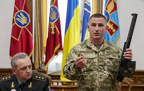 Một chỉ huy Ukraine cầm khẩu súng trường mà ông tuyên bố là tịch thu từ hai nghi phạm binh lính Nga