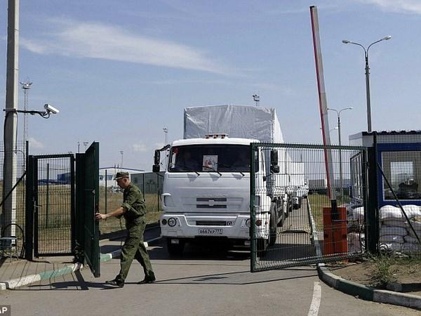 Một binh sỹ mở cửa biên giới để các xe tải chở hàng viện trợ vào Ukraine