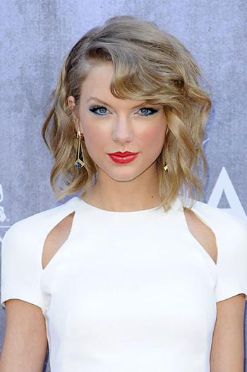 Khi tán son môi đỏ gạch, Taylor Swift kẻ đường viền đuôi mắt bằng chì màu xanh dương, tạo cảm giác tươi trẻ và nổi bật trên nền váy trắng.