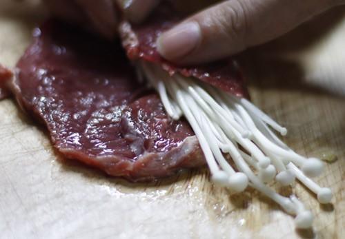 Trải thịt bò thái to bản ra thớt, cho kim châm vào cuốn.