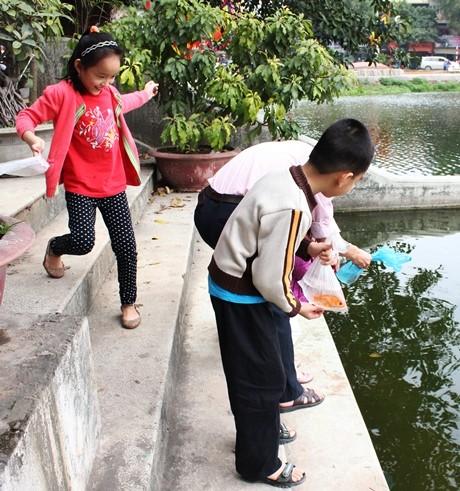 Theo đúng truyền thống hàng năm, anh Ngô Văn Thịnh (40 tuổi, Đội Cấn) lại dẫn con đi thả cá. Lũ trẻ rất háo hức khi được tự tay thả cá vàng xuống hồ.