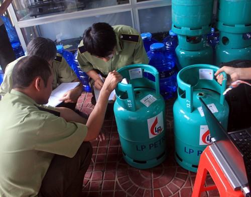 Quản lý thị trường kiểm tra các bình gas của Công ty Long Phụng - Ảnh: Phạm Anh
