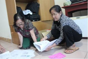 Bà Xoan (mang kính bên phải) với những tài liệu tố cáo ông Quý.