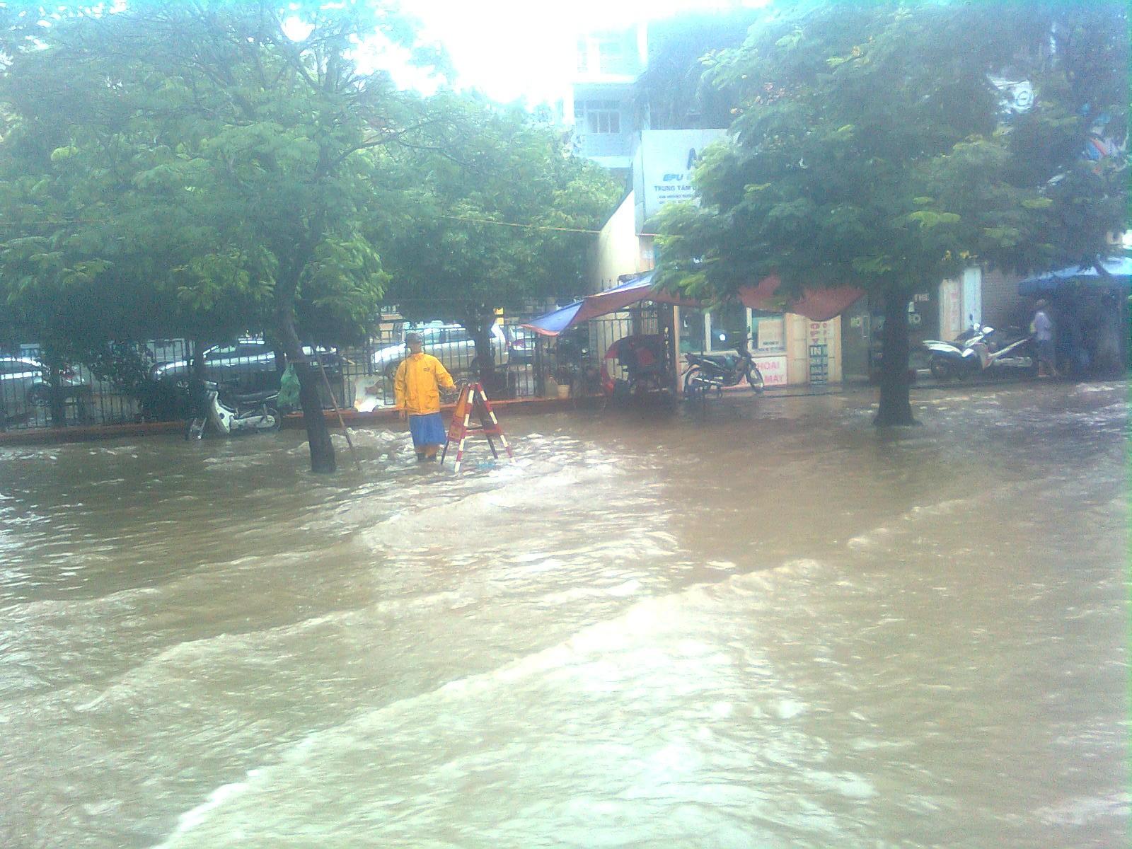 Công nhân đứng trông hố thoát nước trên đường Hoàng Quốc Việt.
