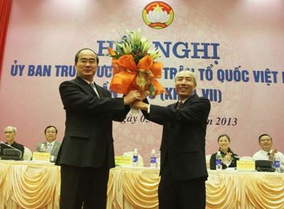 Tân Chủ tịch UB TƯ MTTQ Nguyễn Thiện Nhân nhận hoa chúc mừng của người tiền nhiệm Huỳnh Đảm.