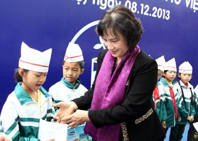 Phó Chủ tịch Quốc hội Nguyễn Thị Kim Ngân trao sữa Vinamilk cho các em học sinh. Ảnh: N. N